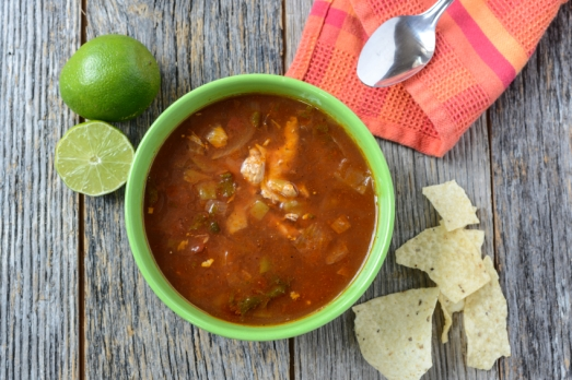 Tortilla Soup with Chips, fresh lime and spoon on Rustic Wood Ba